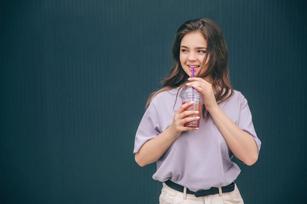 Junge reizende erstaunliche frau, die limonade trinkt und aufwirft