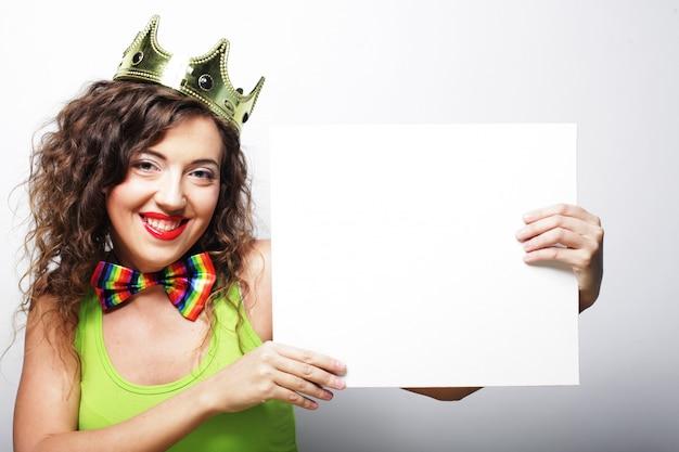Junge reizende frau mit krone und leerem weißem plakat
