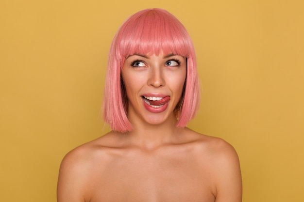 Junge reizende frau mit kurzen rosa haaren, die fröhlich nach oben schauen und ihre zunge herausstrecken, während sie mit nackten schultern über senfwand stehen