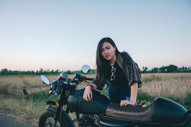 Junge reizvolle frau auf einem motorrad in der natur auf dem sonnenuntergang. reisekonzept.