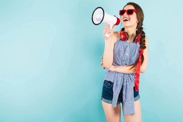 Junge reizvolle frau mit kopfhörern und lautsprecher