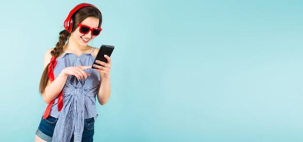Junge reizvolle frau mit kopfhörern und mobiltelefon