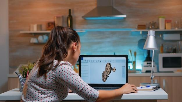 Junge remote-architektin, die an modernen cad-programmüberstunden arbeitet. industrielle ingenieurin, die prototypidee auf pc studiert und cad-software auf dem gerätedisplay zeigt