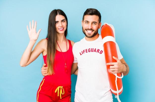 Junge rettungsschwimmerpaar isoliert lächelnd fröhlich zeigt nummer fünf mit den fingern.