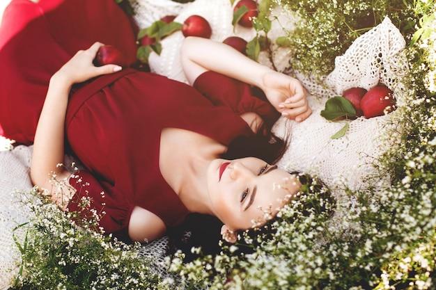 Junge romantische frau im roten kleid, das im sonnigen sommertag des grases liegt