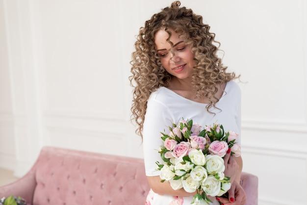 Junge romantische frau zu hause, die auf dem rosa sofa hält einen blumenblumenstrauß und ein träumendes bild sitzt