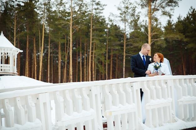 Junge romantische paare des bräutigams und der braut, die auf der brücke stehen und küssen. schöne hintergrundansicht des winterwaldes