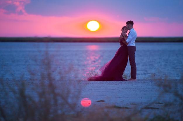 Junge romantische paare, die auf dem strand aufpasst den sonnenuntergang sich entspannen