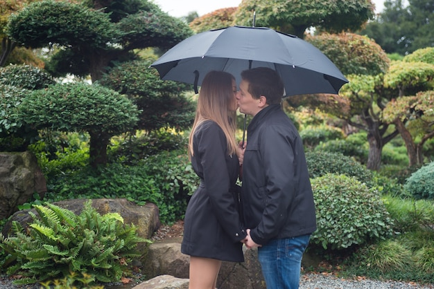 Junge romantische paare, die draußen unter regenschirm küssen