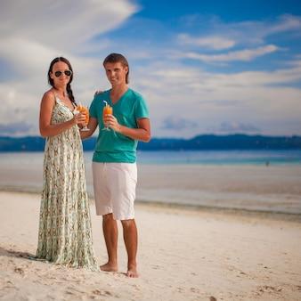 Junge romantische paare, die mit zwei cocktails auf sandigem strand sich entspannen