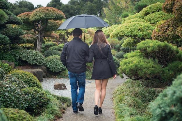 Junge romantische paare, die zusammen in park mit regenschirm gehen