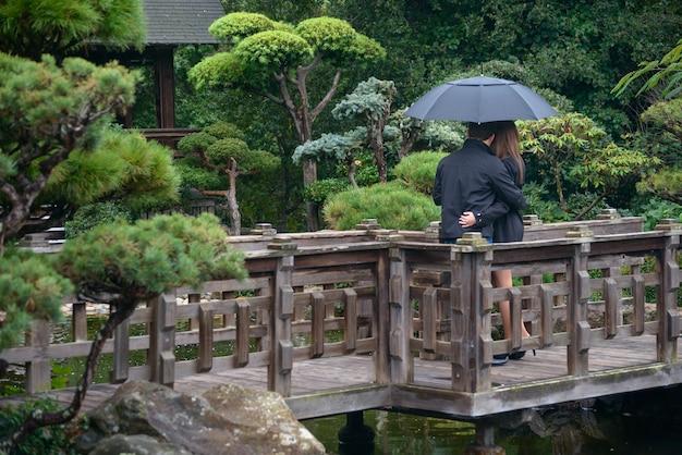 Junge romantische paare mit dem regenschirm, der auf brücke umarmt