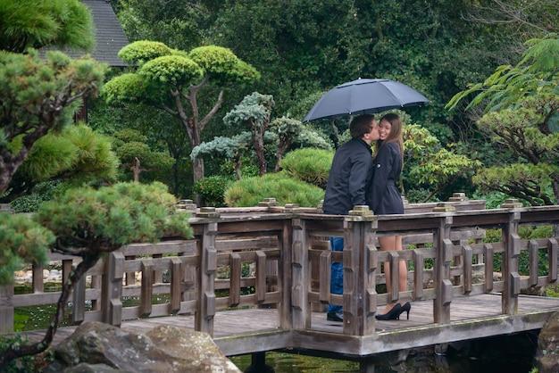 Junge romantische paare mit regenschirm küssend auf brücke