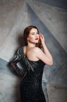 Junge rote haarfrau im schwarzen luxuskleid