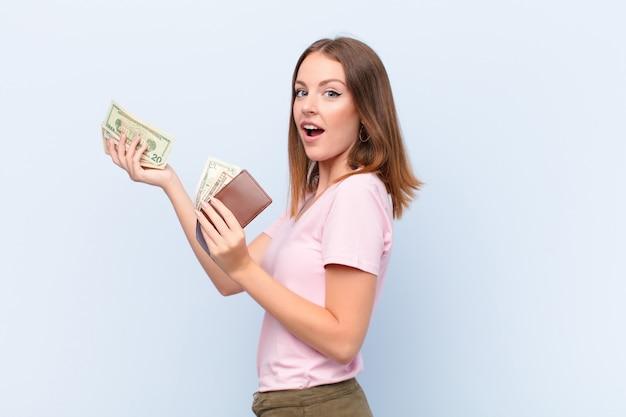 Junge rote hauptfrau gegen geldkonzept der flachen wand