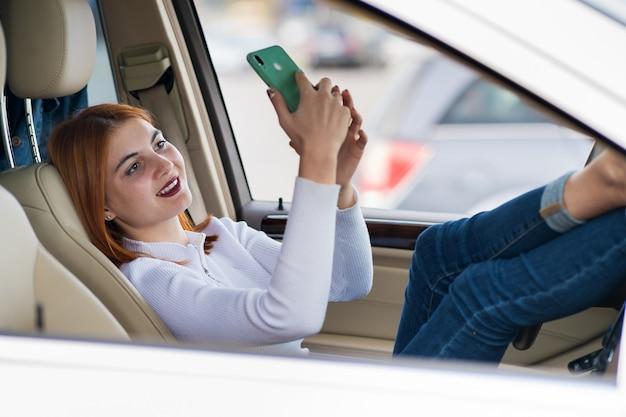 Junge rothaarige fahrerin, die selfies mit ihrem handy nimmt, das hinter dem lenkrad des autos im stau der hauptverkehrszeit sitzt.