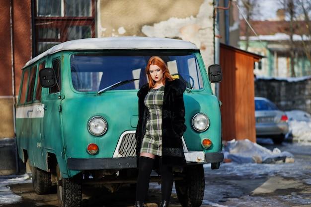 Junge rothaarige frau, die auf kariertem dressand pelzmantel im alten retro- cyan-blauen minivan aufwirft.