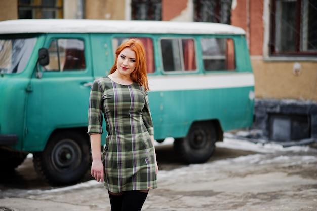 Junge rothaarige frau, die auf kariertem kleid im alten retro- cyan-blauen minivan aufwirft.