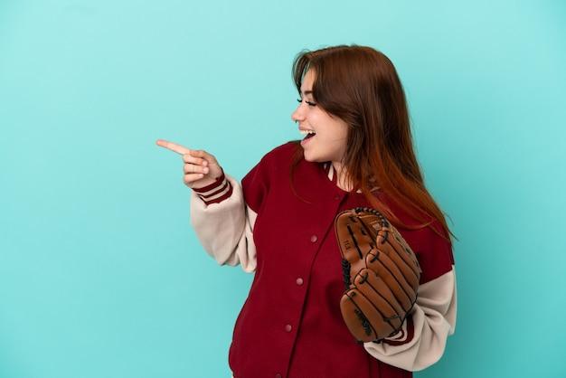 Junge rothaarige frau, die baseball spielt, isoliert auf blauem hintergrund, der mit dem finger zur seite zeigt und ein produkt präsentiert
