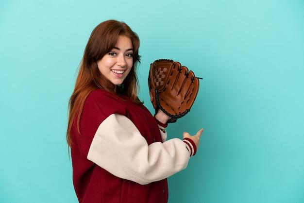 Junge rothaarige frau, die baseball spielt, isoliert auf blauem hintergrund, der nach hinten zeigt