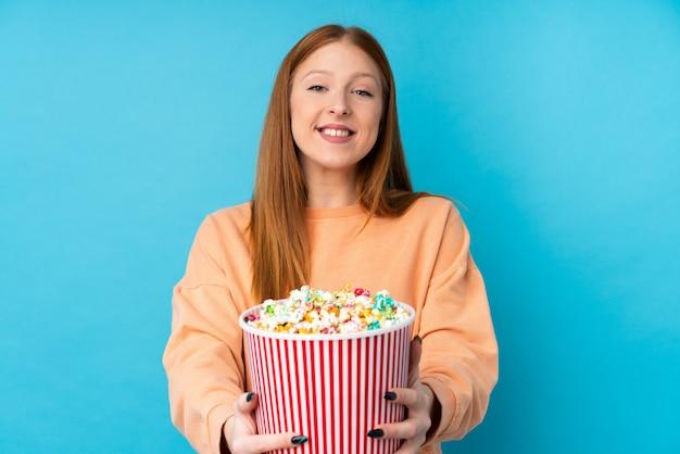 Junge rothaarige frau, die einen großen eimer popcorn hält