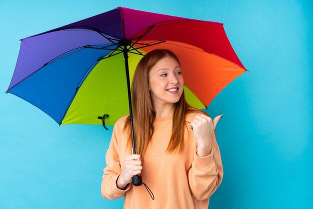 Junge rothaarige frau, die einen regenschirm über isolierter wand hält, die zur seite zeigt, um ein produkt zu präsentieren