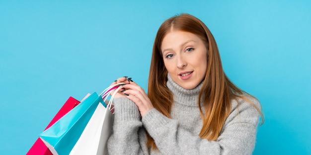 Junge rothaarige frau, die einkaufstaschen hält