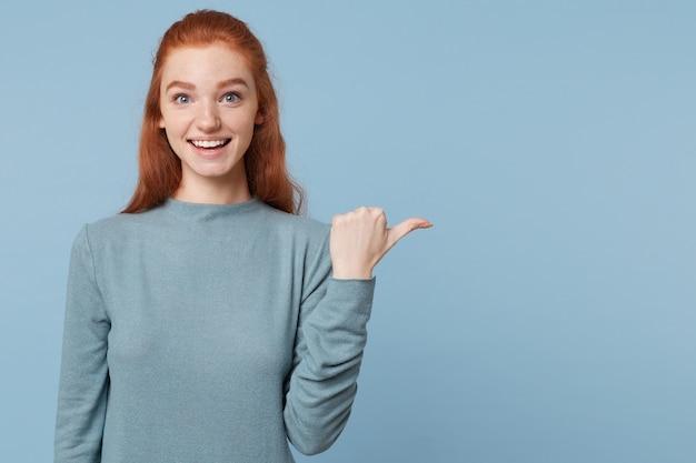 Junge rothaarige frau, die lächelt und glücklich mit ihrem daumen zeigt