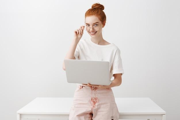 Junge rothaarige frau, die mit laptop arbeitet und brille trägt