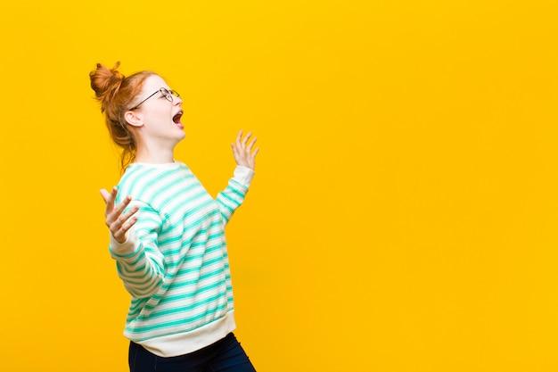 Junge rothaarige frau, die oper durchführt oder bei einem konzert oder einer show singt, romantisch, künstlerisch und leidenschaftlich auf orange wand fühlt