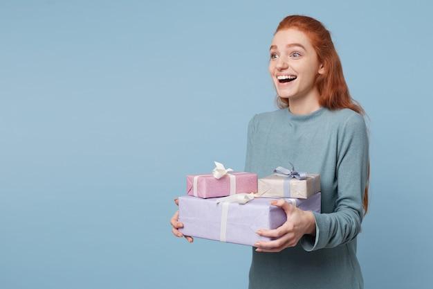 Junge rothaarige frau, die seitlich steht und abstand hält, der kisten mit geschenken hält