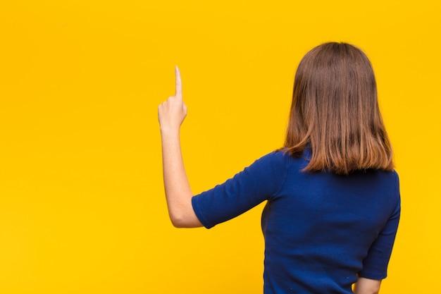 Junge rothaarige frau, die steht und auf objekt auf kopienraum zeigt, rückansicht gegen flache wand