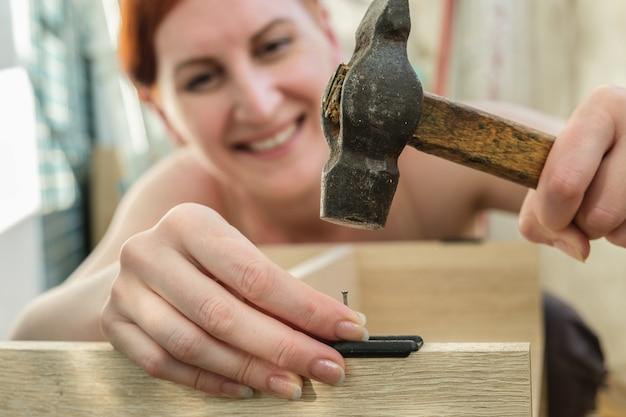 Junge rothaarige frau hämmert in einen nagel und lächelt frau sammelt möbel hausarbeit diy