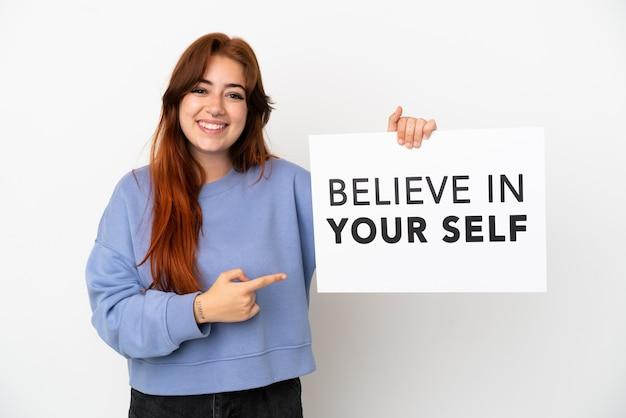 Junge rothaarige frau isoliert auf weißem hintergrund, die ein plakat mit dem text believe in your self hält und darauf zeigt