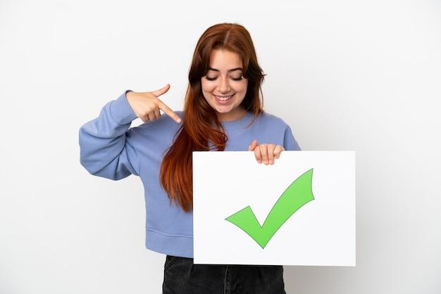 Junge rothaarige frau isoliert auf weißem hintergrund, die ein plakat mit grünem häkchen-symbol hält und darauf zeigt
