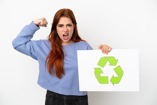 Junge rothaarige frau isoliert auf weißem hintergrund, die ein plakat mit recycling-symbol hält und starke geste macht