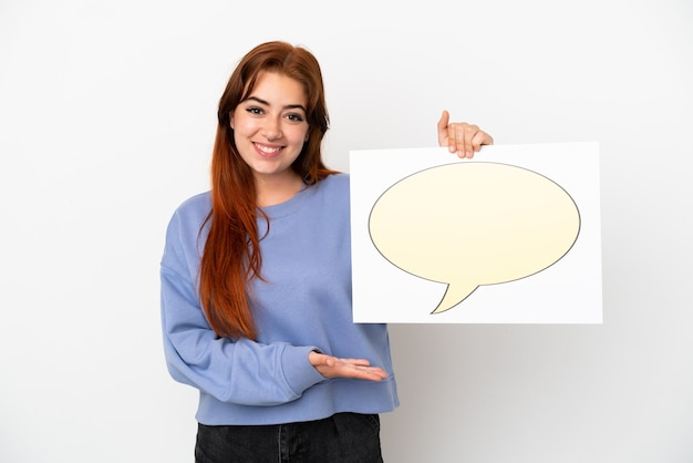 Junge rothaarige frau isoliert auf weißem hintergrund, die ein plakat mit sprechblasensymbol hält und darauf zeigt