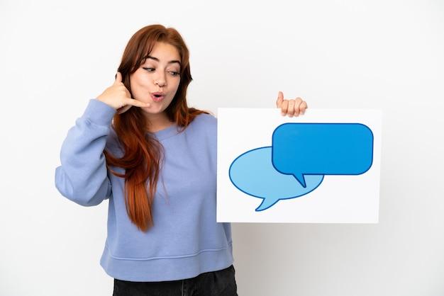 Junge rothaarige frau isoliert auf weißem hintergrund, die ein plakat mit sprechblasensymbol hält und telefongeste macht