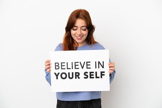 Junge rothaarige frau isoliert auf weißem hintergrund hält ein plakat mit dem text believe in your self