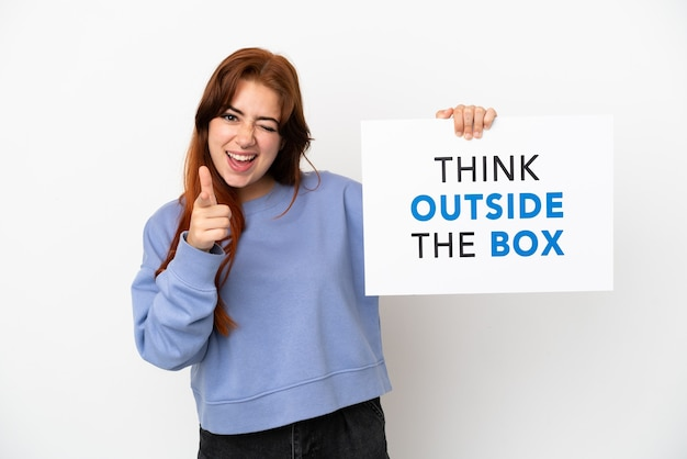 Junge rothaarige frau isoliert auf weißem hintergrund hält ein plakat mit dem text think outside the box und zeigt nach vorne