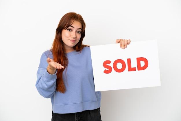 Junge rothaarige frau isoliert auf weißem hintergrund hält ein plakat mit dem text verkauft und macht einen deal