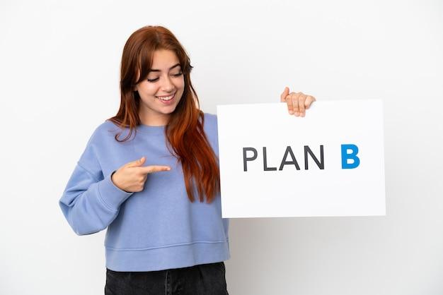 Junge rothaarige frau isoliert auf weißem hintergrund hält ein plakat mit der nachricht plan b