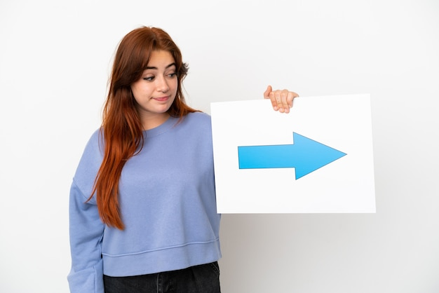 Junge rothaarige frau isoliert auf weißem hintergrund mit einem plakat mit pfeilsymbol
