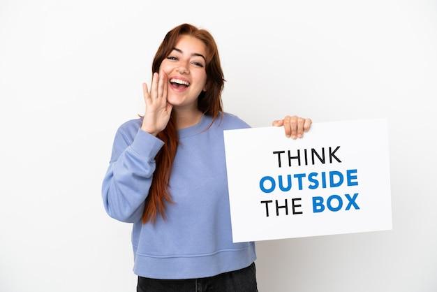 Junge rothaarige frau isoliert auf weißem hintergrund mit einem plakat mit text think outside the box und schreien