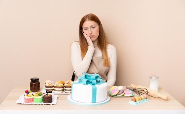 Junge rothaarige frau mit einem großen kuchen unglücklich und frustriert