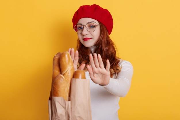 Junge rothaarige frau mit locken weigert sich von frischem brot baguette angebot von unbekannter person auf gelb