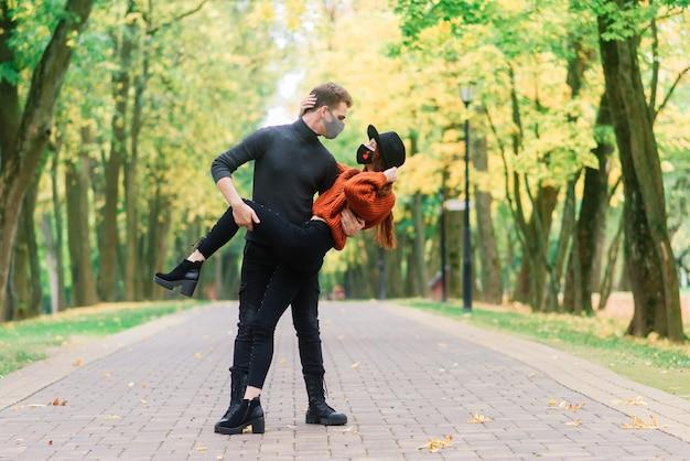 Junge rothaarige frau setzt eine gesichtsmaske auf, während sie mit jungem mann im herbstpark geht