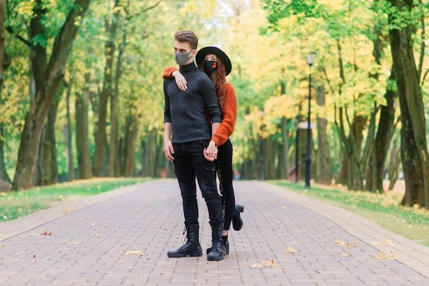 Junge rothaarige frau setzt eine gesichtsmaske auf, während sie mit jungem mann im herbstpark geht.