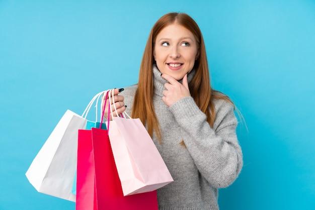Junge rothaarige frau über isolierter blauer wand, die einkaufstaschen hält und denkt