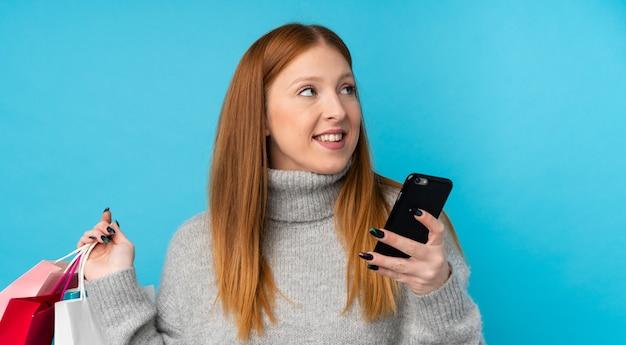 Junge rothaarige frau über isolierter blauer wand, die einkaufstaschen und ein mobiltelefon hält
